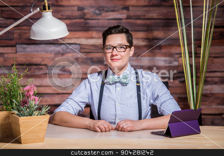 Dapper Woman in Hipster Office with Tablet stock photo, Dapper bowtie wearing woman at stylish office desk with tablet by Scott Griessel