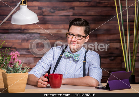 Butch Businesswoman with Coffee Mug stock photo, Smiling Dapper woman at stylish office desk with a red coffee mug by Scott Griessel