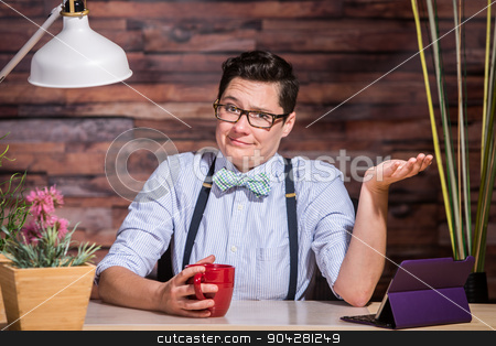 Indifferent Woman in Bowtie stock photo, Indifferent boyish woman at desk with palm up by Scott Griessel