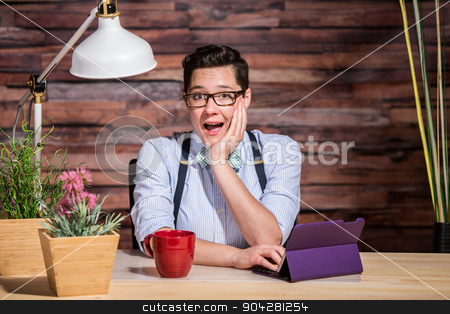 Excited Woman at Desk stock photo, Happy dapper woman wearing glasses and bowtie with cup and tablet computer by Scott Griessel