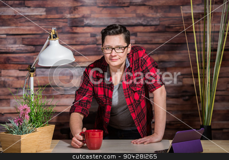 Woman Standing Behind Desk stock photo, Boyish casual businesswoman standing behind desk by Scott Griessel