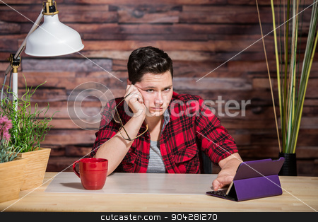 Bored Butch Lady at Desk stock photo, Single bored butch lady at desk with tablet computer by Scott Griessel