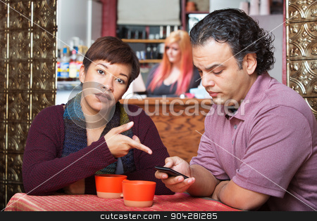 Woman Pointing at Cell Phone stock photo, Annoyed woman pointing at cell phone held by man by Scott Griessel