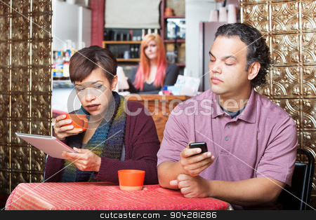 Couple Sneaking with Digital Devices stock photo, Young adult couple at cafe sneaking a peek at their devices by Scott Griessel
