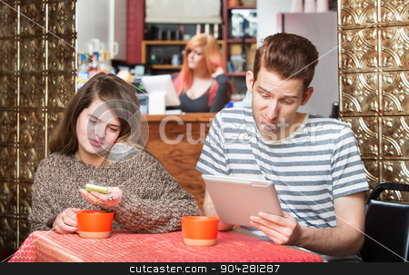 Young Couple at Table with Devices stock photo, Young couple with phone and tablet computer in cafe by Scott Griessel