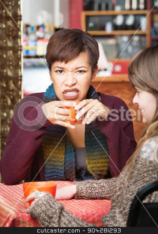 Angry Female Having Coffee stock photo, Woman with clenched teeth holding coffee mug by Scott Griessel