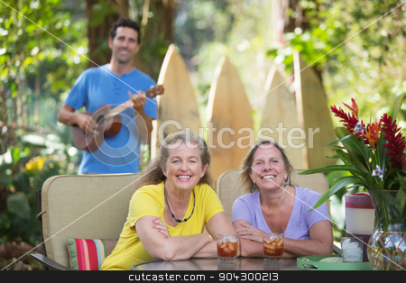Pretty Women Outdoors stock photo, Pair of happy female friends near ukulele player outdoors by Scott Griessel