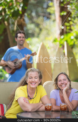 Pretty Female Friends Outdoors stock photo, Two smiling female friends near ukulele player in Hawaii by Scott Griessel