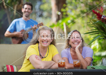Laughing Women In Hawaii stock photo, Pair of laughing female friends near ukulele player outdoors by Scott Griessel