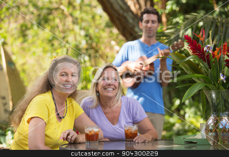 Happy Friends with Ukelele Player stock photo, Two beautiful happy women with male ukelele player by Scott Griessel