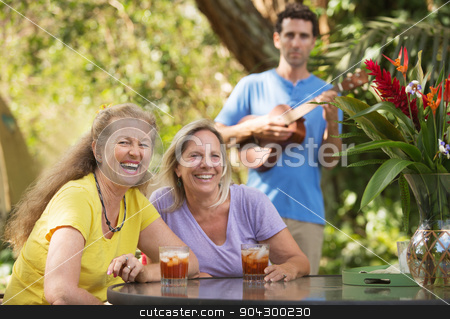 Laughing Women with Ukelele Player stock photo, Two laughing women with ukelele player behind them by Scott Griessel