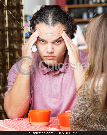Stressed Out Man Holding Head stock photo, Stressed out man rubbing his head at table with friend by Scott Griessel