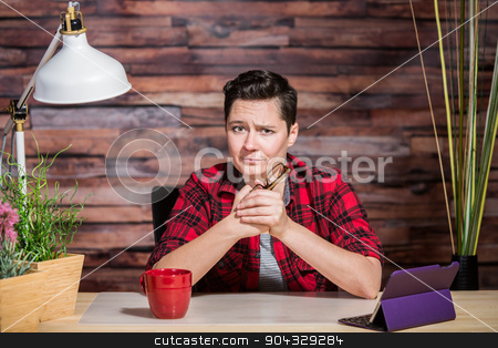 Woman with One Eyebrow Raised stock photo, Woman wearing flannel shirt at desk with one eyebrow raised by Scott Griessel