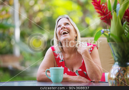 Laughing Woman Sitting at Table stock photo, Attractive single mature woman at table laughing by Scott Griessel