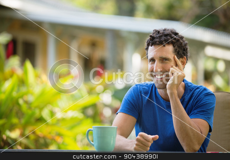 Laughing Man Sitting Outdoors stock photo, Laughing man with coffee sitting outdoors in Maui by Scott Griessel