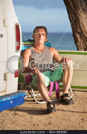 Attractive Man Sitting with Surfboard stock photo, Attractive calm man sitting with surfboard behind him by Scott Griessel