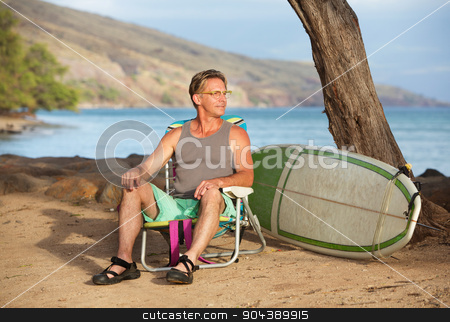 Surfer on Beach with Surfboard stock photo, Handsome male surfer sitting on beach near his surfboard by Scott Griessel