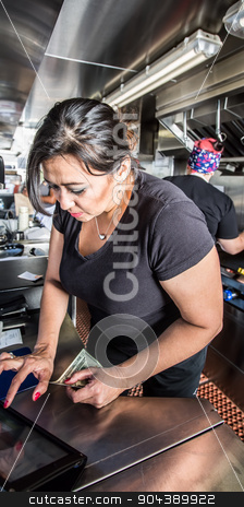 Cashier with Money in Food Truck stock photo, Female cashier with money on busy food truck by Scott Griessel