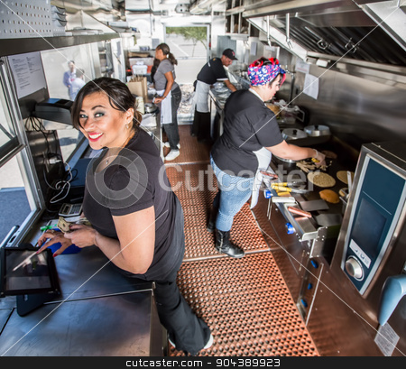 Happy Cashier in Busy Food Truck  stock photo, Happy cashier with payment on busy food truck by Scott Griessel