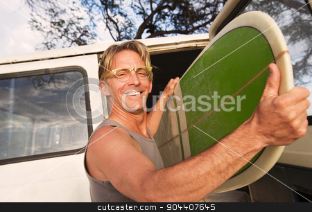Happy Man Removing Surfboard stock photo, Happy man removing surfboard from of his van by Scott Griessel