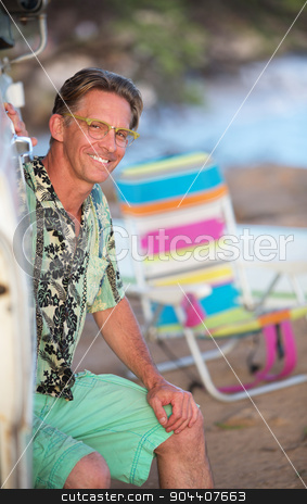 Smiling Man Sitting on Beach stock photo, Cute adult Caucasian male outdoors sitting on beach by Scott Griessel