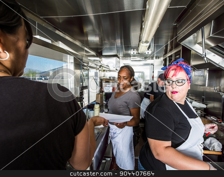 Preparing Food on Busy Food Truck stock photo, Female chef with pink hair works alongside crew on food truck by Scott Griessel
