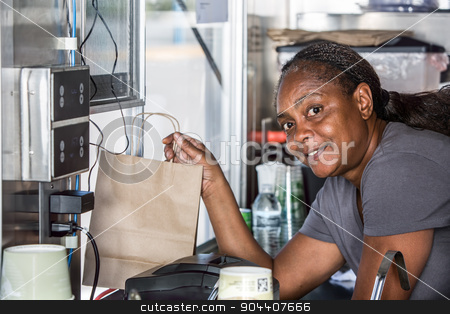 Smiling African-American Worker Hands Food Order Out Window stock photo, Smiling African-American worker hands order out window of modern food truck by Scott Griessel