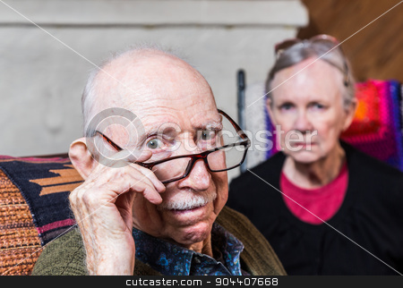 Concerned Elderly Couple stock photo, Concerned elderly couple sitting in livingroom scowling by Scott Griessel