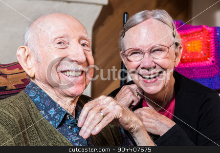 Happy Older Couple stock photo, Happy older couple sitting in living-room smiling at camera by Scott Griessel