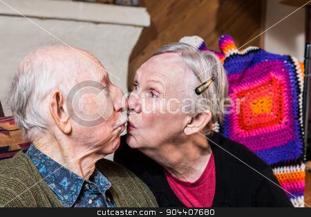 Elderly Couple Kissing stock photo, Happy elderly couple sitting in livingroom kissing by Scott Griessel
