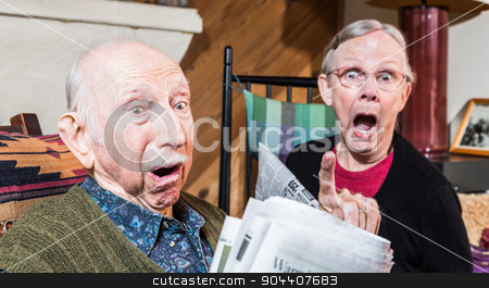 Angry Old Couple with Newspaper stock photo, Angry older couple reading newspaper in living-room by Scott Griessel