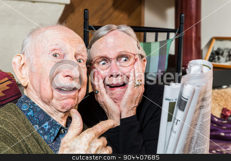 Shocked Older Couple with Newspaper stock photo, Shocked older couple looking at the newspaper in their living-room by Scott Griessel