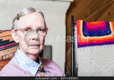 Elderly Woman in Livingroom stock photo, Elderly woman in pink sweater seated in living room by Scott Griessel