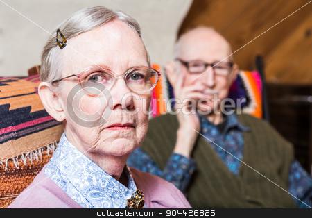Elderly Couple Sitting in Livingroom stock photo, Elderly couple looking seriouds seated in livingroom by Scott Griessel
