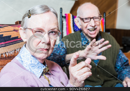 Angry Old Couple in Livingroom stock photo, Angry old couple sitting in living room woman pointing by Scott Griessel