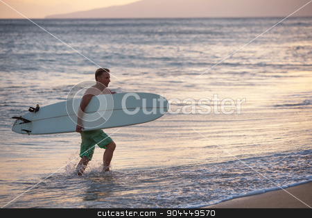 Carrying Surfboard Out of Water stock photo, European man carrying his surfboard out of the water by Scott Griessel