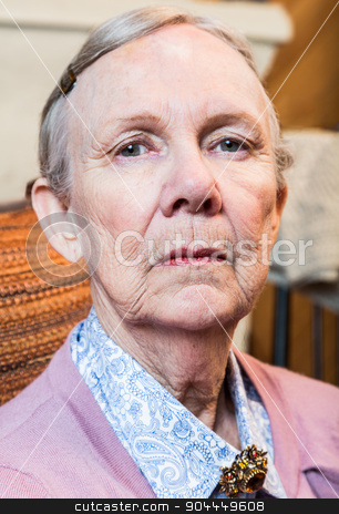 Stern Elderly Lady stock photo, Stern elderly lady in pink sweater looking down at camera by Scott Griessel