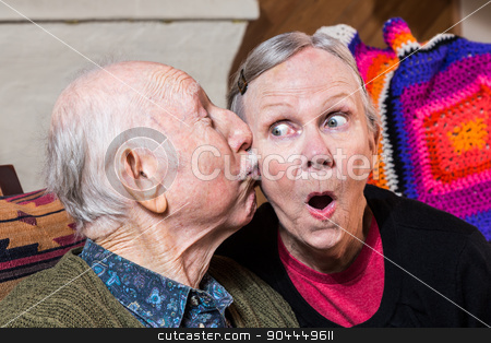 Elderly Gentleman Kissing Elderly Woman on Cheek stock photo, Elderly gentleman kissing elderly woman on cheek in livingroom by Scott Griessel