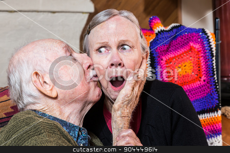 Older Gentleman Kissing Older Woman on Cheek stock photo, Older gentleman kissing older shocked woman on cheek in livingroom by Scott Griessel