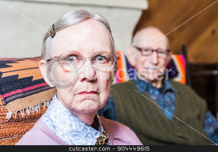 Serious Man and Woman Indoors stock photo, Old couple seating in livingroom woman scowling by Scott Griessel