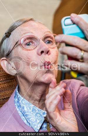 Happy Elder Woman taking Selfie stock photo, Happy elder woman taking duck face selfie by Scott Griessel