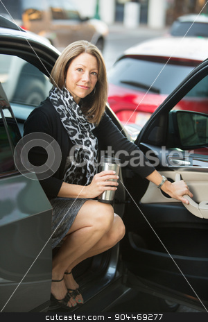 Happy Woman Sitting in Car stock photo, Happy executive woman with scarf sitting in open car by Scott Griessel