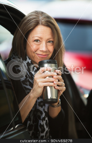 Woman Holding Coffee Thermos stock photo, Cheerful mature adult woman holding coffee thermos by Scott Griessel
