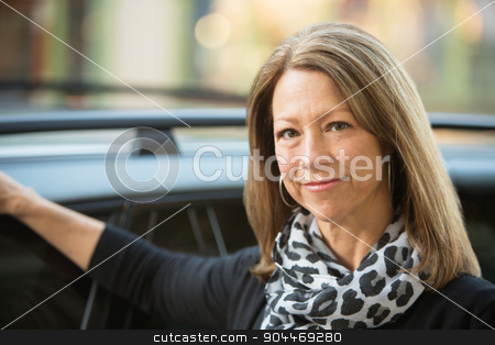 Cute Woman Outside Car stock photo, Cute mature adult business woman outdoors next to car by Scott Griessel