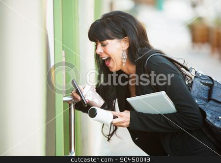 Multitasking Woman Opening Door stock photo, Attractive woman with her hands full attempting to open a door by Scott Griessel