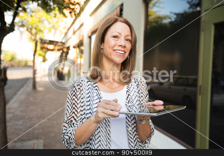 Happy Adult with Tablet Computer stock photo, Happy adult female walking outdoors with tablet computer by Scott Griessel