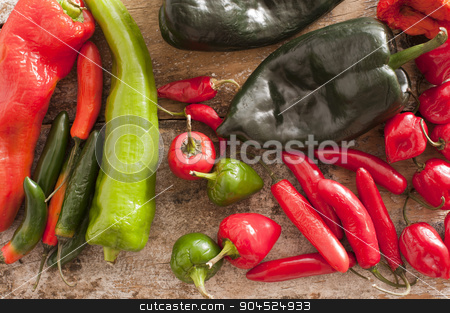 Red and Green Chili Peppers on a Wooden Table stock photo, High Angle View of Assorted Red and Green Chili Peppers on a Rustic Wooden Table. by Stephen Gibson