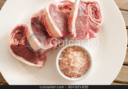 Fresh Lamb Meat Chops on Plate with Salt stock photo, Top View of Fresh Lamb Meat Chops on White Round Plate with Rock Salt on a Saucer. by Stephen Gibson