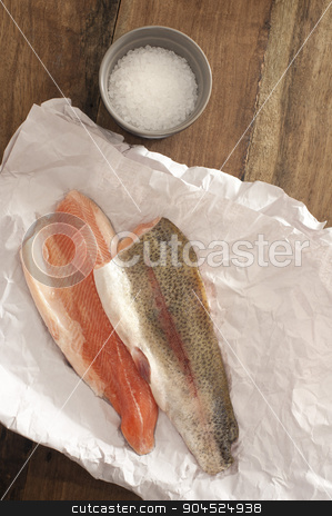 Rainbow Trout Meat on a Table with Salt stock photo, Top View of Fresh Rainbow Trout Meat on a Paper Placed on Wooden Table with Rock Salt on a Saucer. by Stephen Gibson