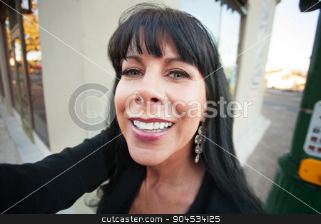 Woman Takes a Selfie Outdoors stock photo, Pretty woman takes a selfie on downtown street by Scott Griessel